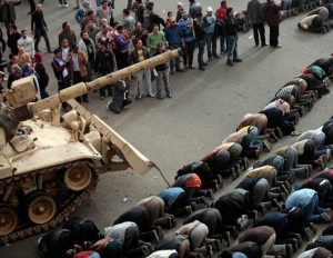 egypt-protesters-praying-near-tank-300x232