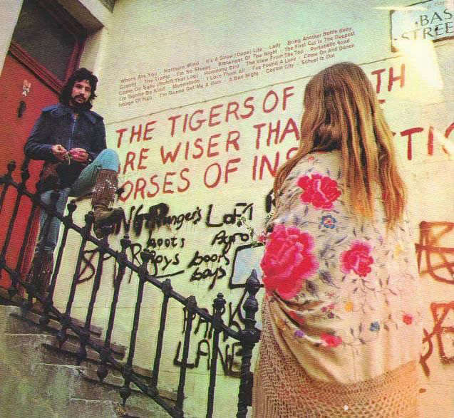 """Cat Stevens photographed by the William Blake graffiti """"The tigers of wrath are wiser than the horses of instruction"""" on the corner of Lancaster Road and Basing Street in London (1970)."""