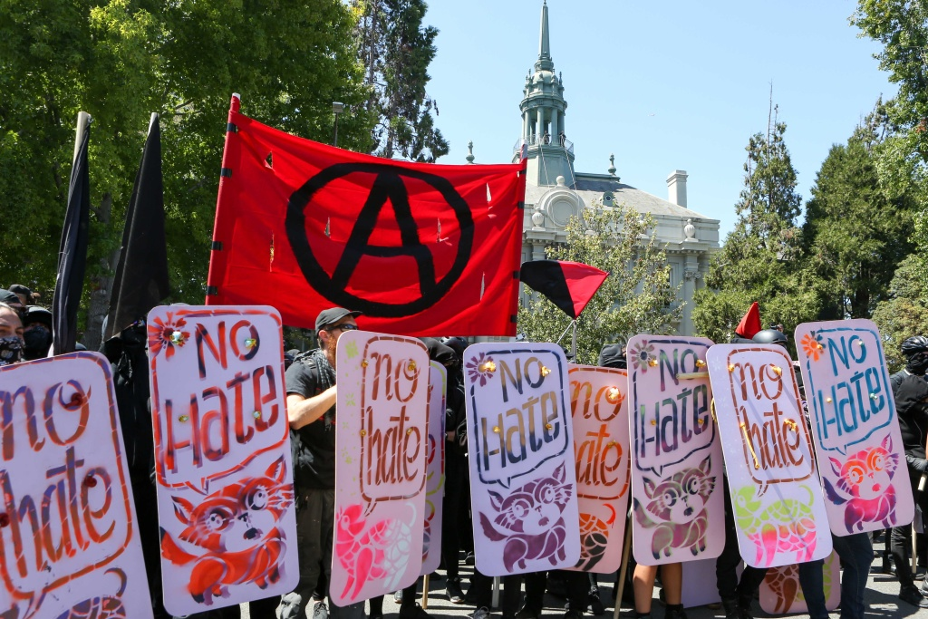 """Anarchists and anti-fascists hold """"no hate"""" shields at the counter-protest for """"No To Marxism"""" rally in Berkeley, California, on August 27, 2017."""
